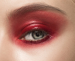 Close-up shot of female eye with red makeup