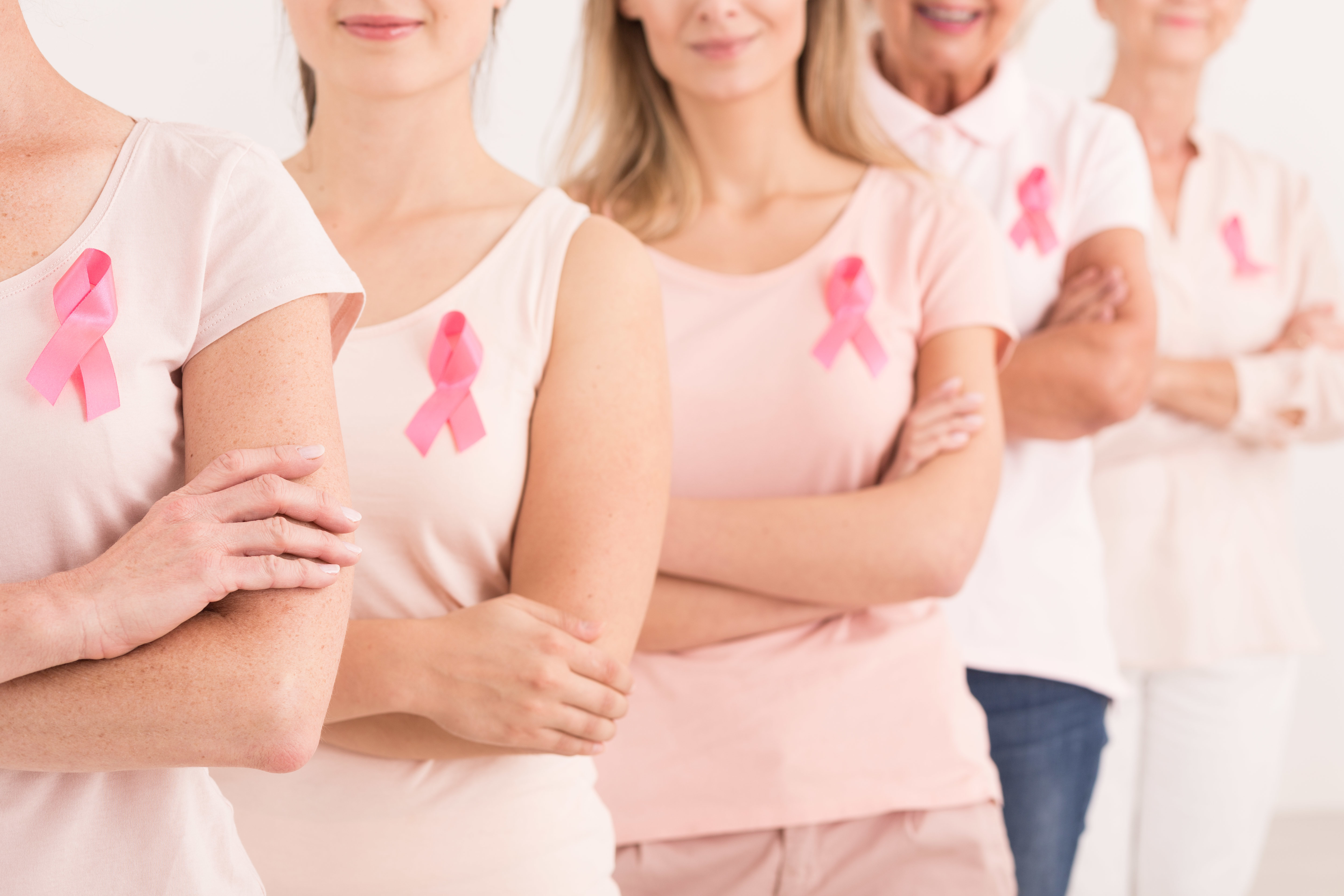 The power to fight breast cancer, women wearing pink ribbons for breast cancer campaign on white background
